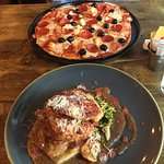 Pepperoni, goats cheese and olive pizza and parmesan and oregano crusted chicken