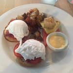 Poached eggs on a muffin Hollandaise on the side Fruit stack and potatoes.
