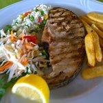 Swordfish steak served with chips, rice, salad