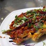 """香料鮭魚咖哩,是店裡招牌菜之一,將新鮮鮭魚在印度式的平底鍋""""Tawa""""上煎至金黃酥脆,再淋上特製的香料咖哩,深受各國客人喜愛。"""