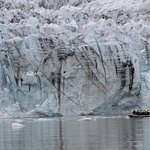 Tour boat close to glacier wall. There is quite a distance between boat and wall for safety,