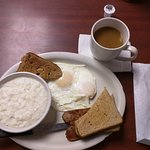 A white and brown breakfast of eggs, grits, wheat toast & coffee.