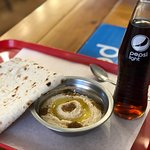 side of hummus with fresh lavash flat bread and Pepsi light.