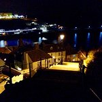 Steps up to Whitby Abbey at night with views of narrow cobbled streets and harbour below