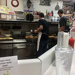 Two men at grill struggle to keep up with orders.