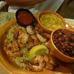 grilled shrimp on rice, beans and corn