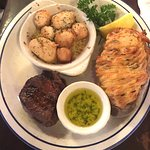 Petite filet with baked scallop and a baked stuffed potato, garlic butter sauce