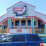 This is the front of the Oyster House. It is part of a small shopping strip. It is bright and su