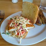 Chicken sandwich with spicy cole slaw topping and potato wedges. Delicious!