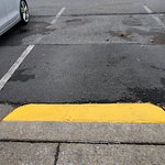 Yellow ramp to sidewalk at Rockville Shopping Center for Duck Donuts.