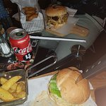 The Lots of cheese burger and Sun of a bun burgers with fries and onion rings sides