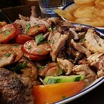 Meat platter and slow cooked potatoes. A Greek food feast.