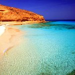 It is characterized by its clear blue waters. This beach is located in front of a giant rock.