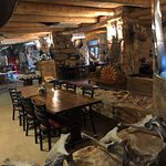 Rustic with lots of old wood and stone - several dining areas