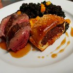 Roast venison with rich game sausage roll