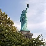 Lady Liberty appears as you walk past trees. Stunning!
