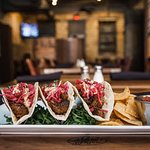 Brisket Tacos. House-smoked brisket, mustard aioli, and red slaw. Served with chips and salsa.