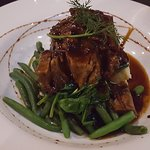 Pork with plum sauce on a bed of mash, spinach and green beans.