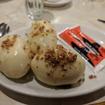 This is the Cepelinai. It is a potato dumpling stuffed with ground meat. Sour cream on the side.