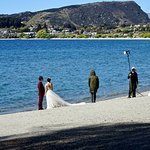 Bride and Groom on Lake Shore, Heading to Photo Shoot at Tree