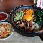 Korean bibimbap Hotpot with crunchy rice, vegetables, egg yolk, sriracha sauce & kim chi