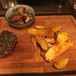 Steak and fries served on wooden board