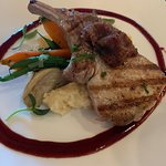 Bone-in pork chop with bacon jam and blackberry barbecue sauce