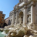 Statues, a building facade, and flowing water