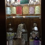 Wall mounted cabinet with a selection of gins and tonics.