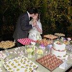 Mesa do bolo e doces com o jardim vertical ao fundo.