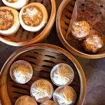Clockwise from top left: char-siu bao, shrimp and pork siu mai, and xiao long bao (soup dumpling