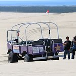 Big purple dune buggy on sand dunes with Pacific Ocean in the distance