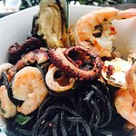 Black squid ink pasta sautéed with seafood in extra virgin olive oil,roasted garlic, tomato conc