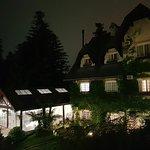 Visão noturna parcial do hotel, do seu jardim e piscina a partir da janela do quarto 207.