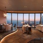 """海岸餐厅&酒吧(54 楼)是一间时尚别致的特色餐厅及酒吧,主要提供上等海鲜、精品进口肉类等多种烧烤佳肴。独立的吧台区域是享受餐前小酌的理想场所。置身于厦门最高位置的酒吧,从丰富的窖藏中点一款中意的葡萄酒,或细品调酒师现场特调的鸡尾酒,将是绝佳不凡的体验。新上任特色风味厨师长Alessandro,拥有20多年的西厨烹饪经验,将独具特色的""""地中海风味烧烤""""融入海岸的料理中,带领众食客开启一场全新的味觉盛宴。"""