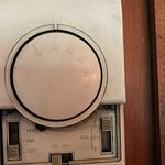 Filthy thermostat on bedroom wall.