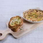 Seafood cream gratin topped with cheddar and mozzarella cheese served with toasted