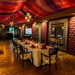 Lush drapery and ornate auburn wall decor adds mystery and charm to the restaurant's ambiance