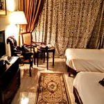 Room on the fifth floor in the main building. Behind curtains : balcony with view on Nile, garden and 2 pools. In the room: 2 single beds,mini fridge and satellite tv. Of course also a bath room.