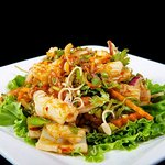 Plah Muk~  Calamari Salad with Fresh Mint Leaves, Onions, Lemons, and Chili Sauce over Salad