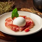 Burrata Pugliese, Pomodorino, Crudo di Parma  Creamy stretched curd cheese served with seasonal sweet tomatoes, Mediterranean herbs and slices of parma ham.