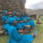 Ladies in traditional dress singing outside their stone homes.