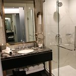 Ruime badkamer met grote douche, grote wastafel en toilet.
