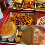 Sliced brisket and sweet potato fries, beans and hush puppies.