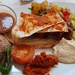 Kabab - skewered minced lamb in a tomato sauce with hummus, salad and rice.