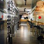 Entrada de QuiebraTinajas, con una barra alta y taburetes al lado de nuestro mostrador de vinos