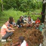 grandes y niñxs colaboran con la limpieza de la cúrcuma, mientras se comparten anecdotas y jugos naturales de frutas tropicales.