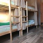 место на двухъярусной кровати в восьми местом номере, общая кухня и ванная комната. Чистое белье, полотенца, запирающийся шкафчик, розетка и ночник у каждого места. Ежедневная уборка.