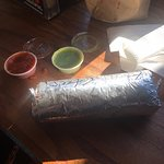 Massive burrito with free spicy sauces on the side.