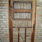A porta do AP rústica,fabricada artesanalmente, com palha de carnaúba,tem aberturas controladas por fio de naylon. AMEI